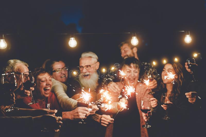 Happy family having at dinner party outdoor - Group of multiracial older and young people celebrating together drinking wine royalty free stock photos