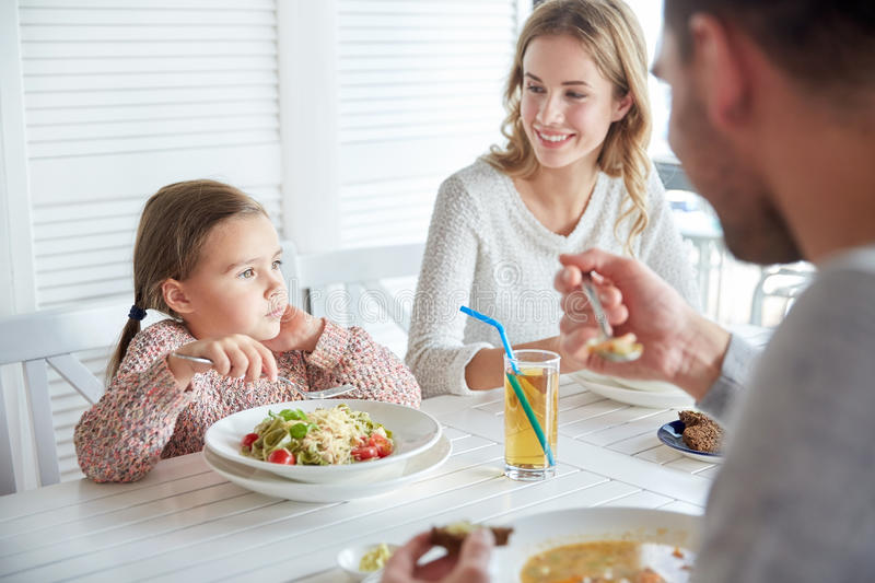Happy family having dinner at restaurant or cafe. Family, parenthood, food and people concept - happy mother, father and little girl eating pasta and soup for royalty free stock photos