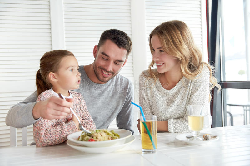 Happy family having dinner at restaurant or cafe. Family, parenthood, food and people concept - happy mother, father and little girl eating pasta for dinner at stock images