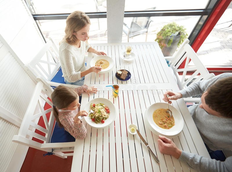 Happy family having dinner at restaurant or cafe. Family, parenthood, food and people concept - happy mother, father and little girl eating soup and pasta for royalty free stock images