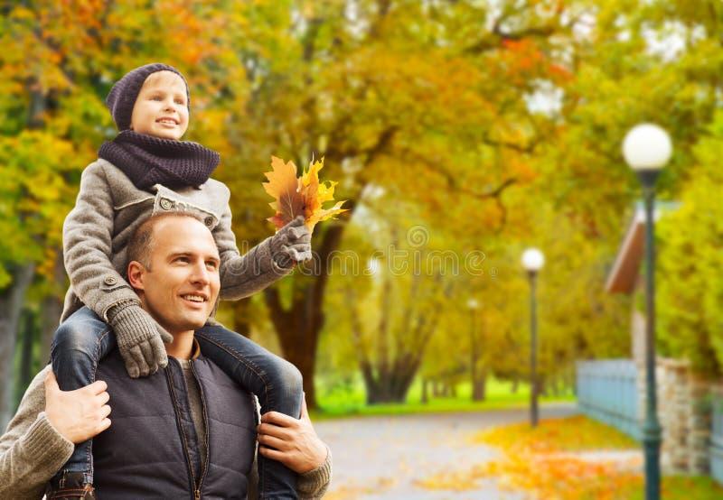 Happy family having fun in autumn park stock photography
