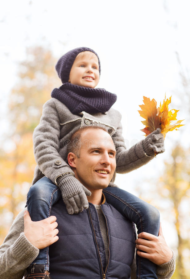 Happy family having fun in autumn park. Family, childhood, season and people concept - happy father and son having fun in autumn park stock image