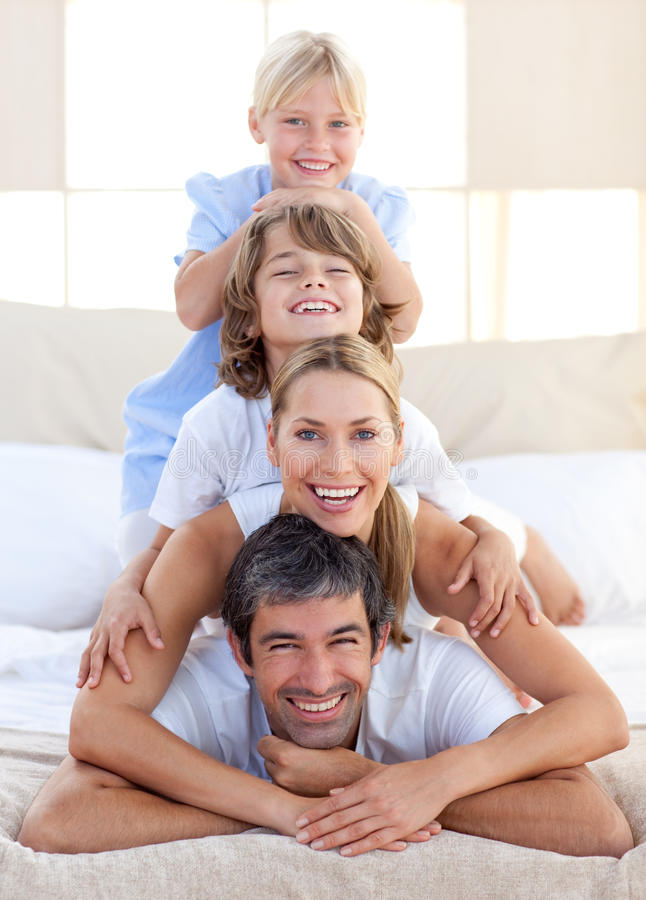 Happy family having fun on a bed stock photos