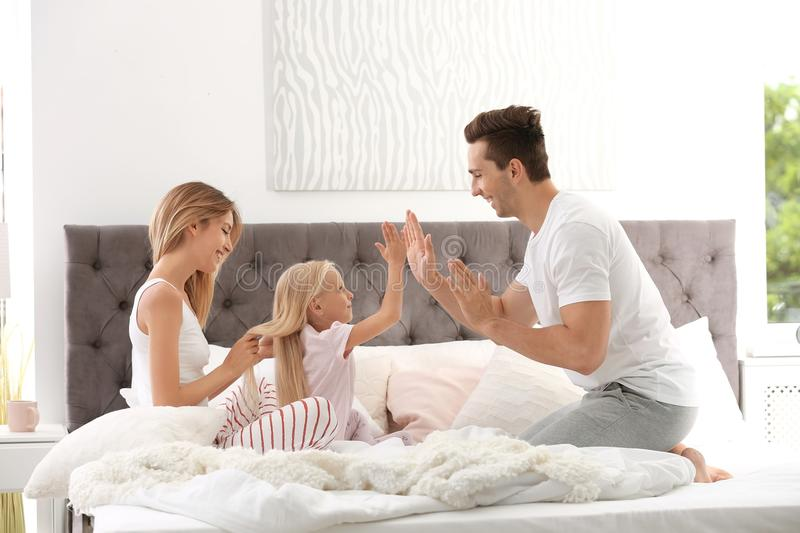 Happy family having fun on bed with pillows stock photography