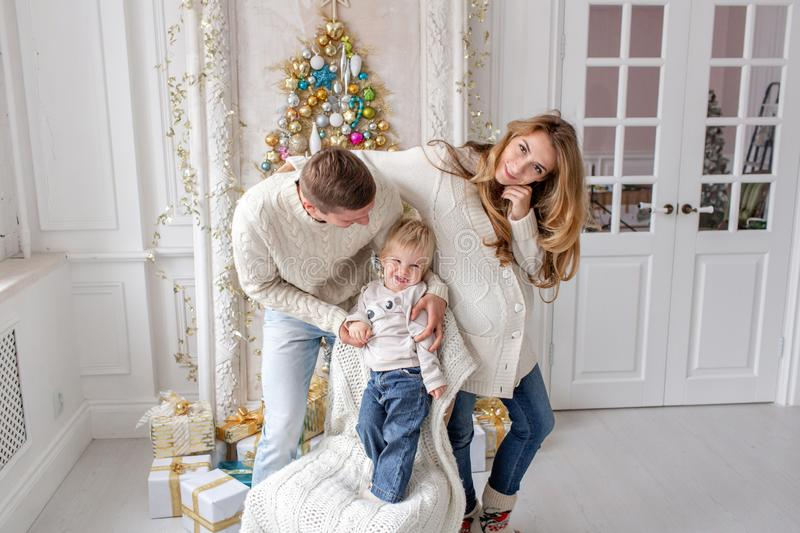 Happy family Portrait In Home - father, pregnant mother and their little son. Happy new year. decorated Christmas tree stock photos