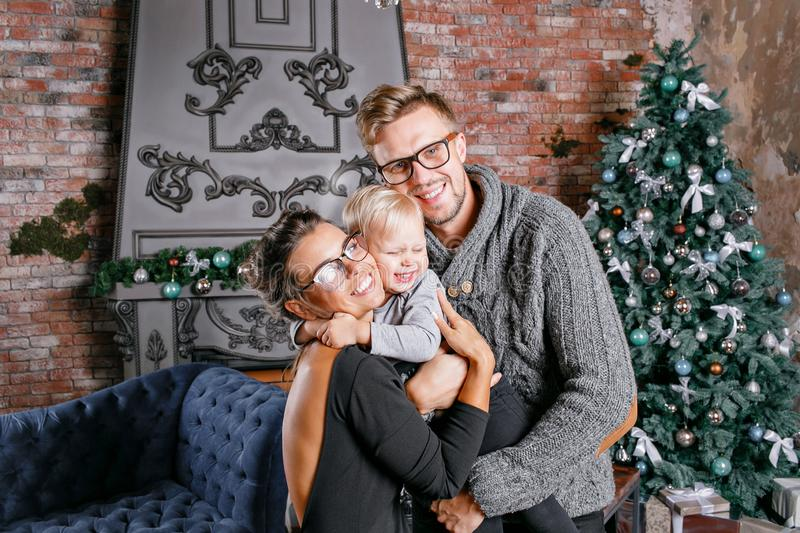 Happy family having fun at home. In loft room with brick wall. Young parents with little son. father, mother and their royalty free stock image