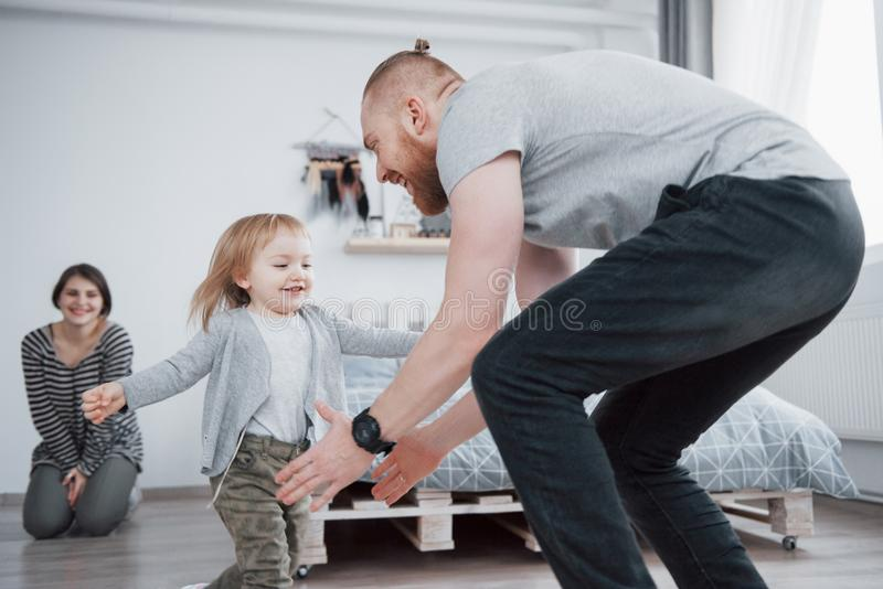 Happy family is having fun at home. Mother, father and little daughter with plush toy are enjoying being together royalty free stock images