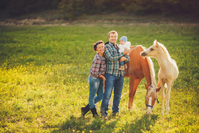 Happy family having fun with horses outdoors on green field on summer day