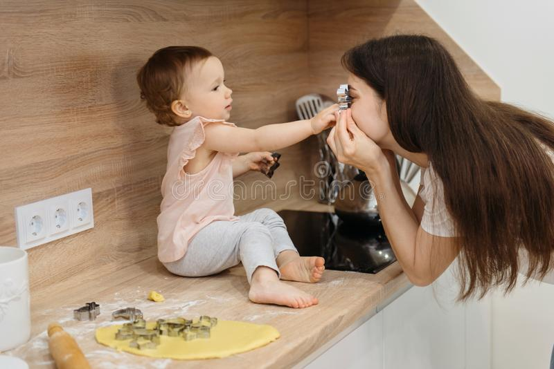 Mother and child daughter preparing the dough, bake cookies royalty free stock photography
