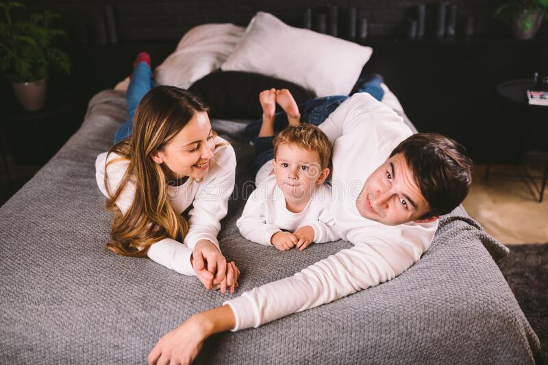 Happy family having fun lying down on bed at home. Happy Family In Bed. Mom dad and son lie on bedroom at within doors stock photography