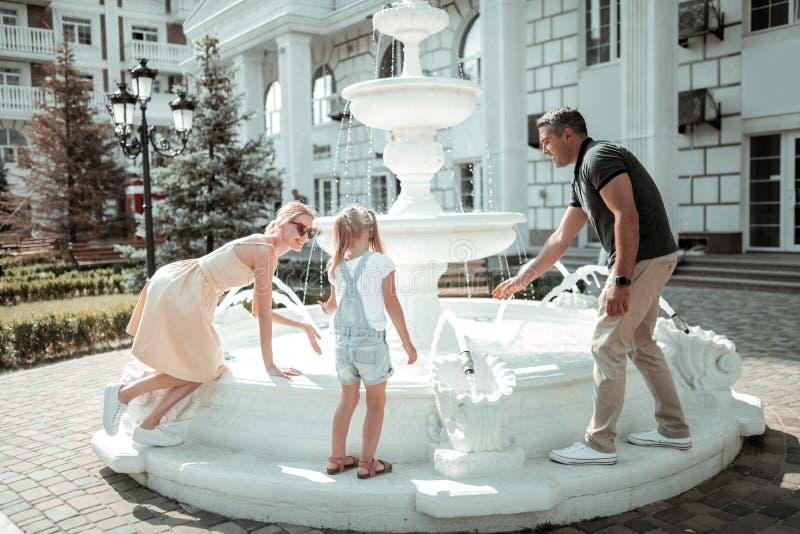 Happy family having fun near the fountain. stock image