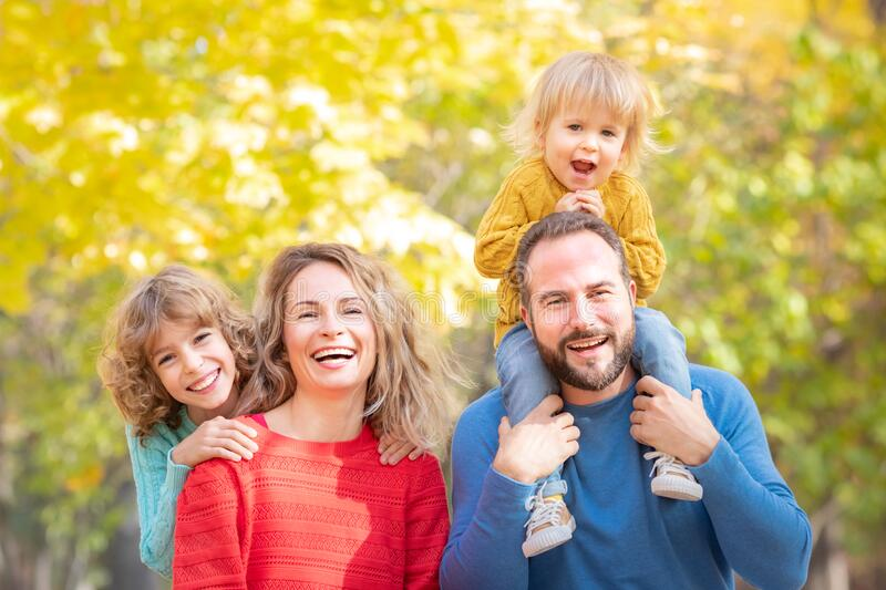 Happy family having fun outdoor in autumn park stock photos
