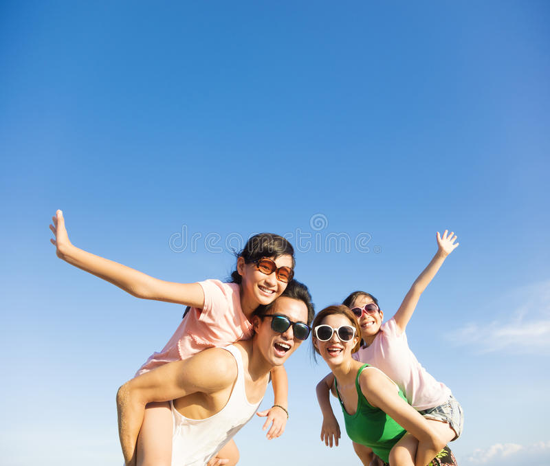 Happy family having fun outdoors against blue sky. Background stock images
