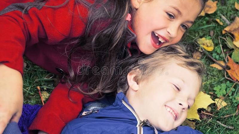 A happy family having fun in the park in autumn. Family, love, happiness concept. Brother and sister hugging and lying royalty free stock photo
