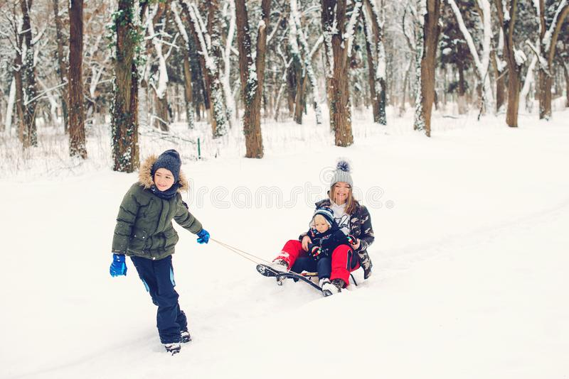 Happy family having fun in snowy park. Children and mother playing in winter time. Active healthy lifestyle. Winter christmas stock image