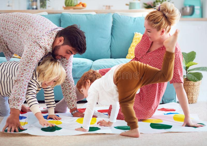Happy family having fun together, playing twister game at home stock photos