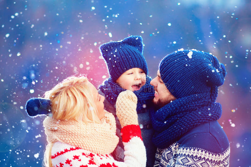 Happy family having fun under winter snow, holiday season stock photo