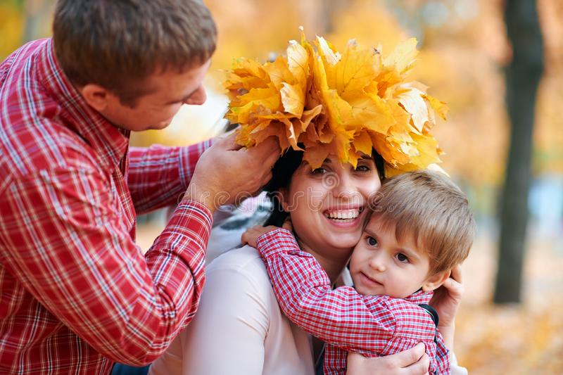 Happy family having holiday in autumn city park. Children and parents making wreath from yellow leaves and having fun. Bright royalty free stock photo