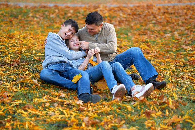 Happy family having holiday in autumn city park. Children and parents posing, smiling, playing and having fun. Bright yellow trees royalty free stock photography