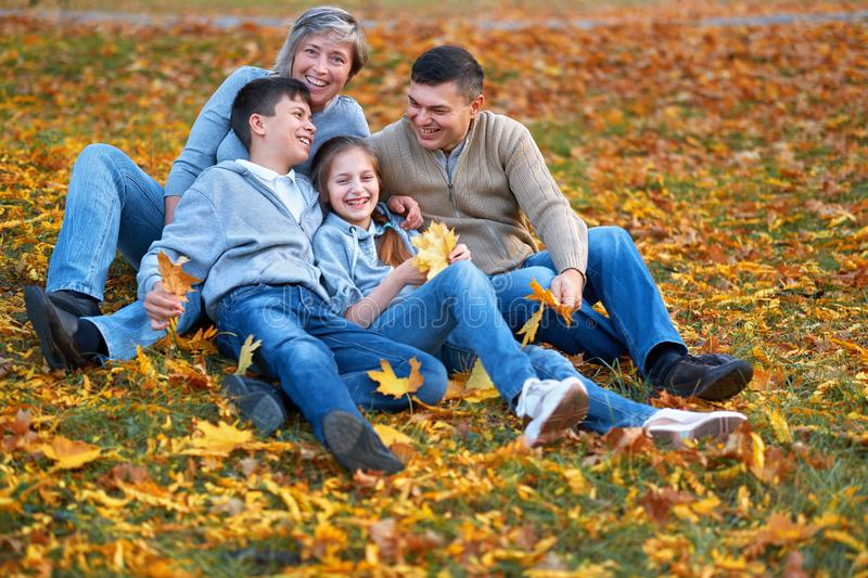 Happy family having holiday in autumn city park. Children and parents posing, smiling, playing and having fun. Bright yellow trees stock images