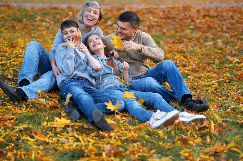 Happy family having holiday in autumn city park. Children and parents posing, smiling, playing and having fun. Bright yellow trees stock photography