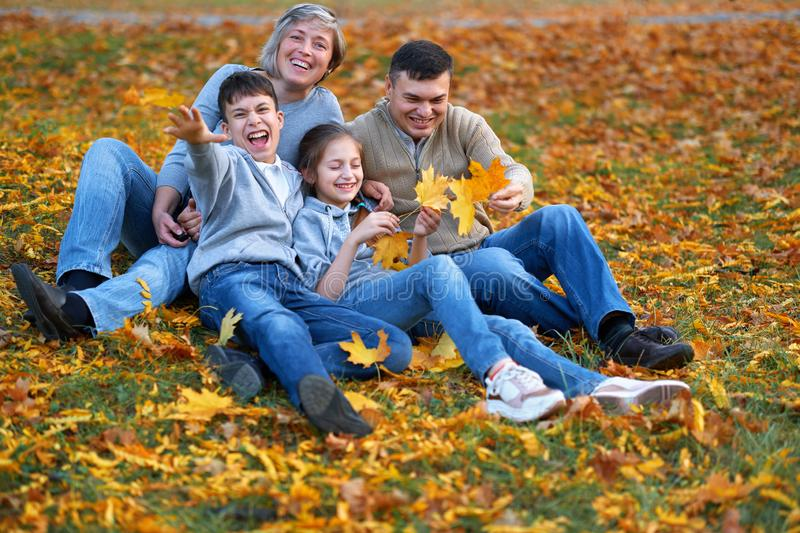 Happy family having holiday in autumn city park. Children and parents posing, smiling, playing and having fun. Bright yellow trees royalty free stock photo