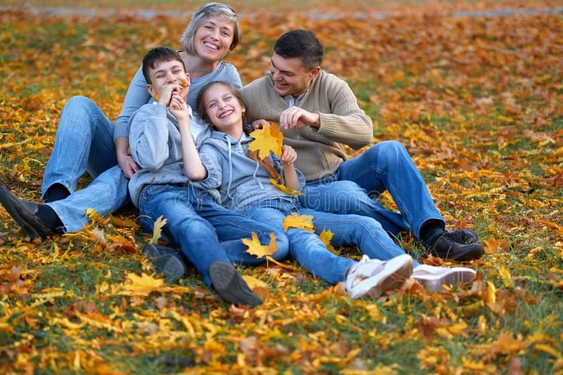 Happy family having holiday in autumn city park. Children and parents posing, smiling, playing and having fun. Bright yellow trees stock photo