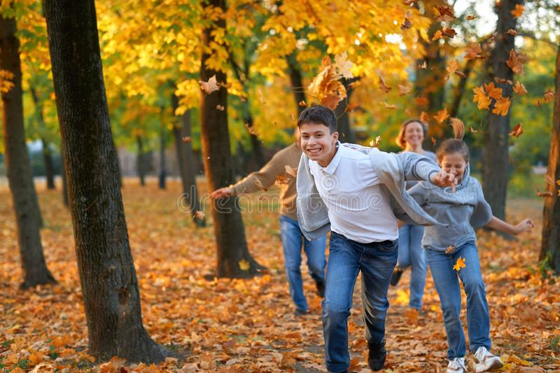 Happy family having holiday in autumn city park. Children and parents running, smiling, playing and having fun. Bright yellow stock photo