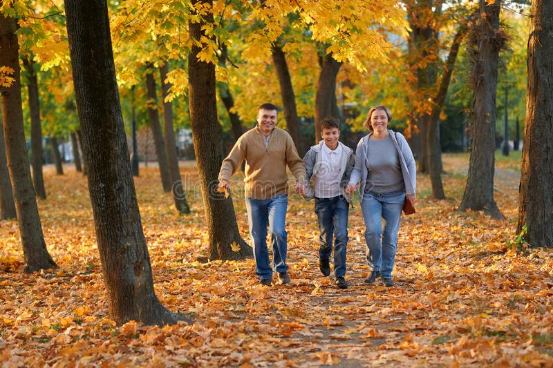 Happy family having holiday in autumn city park. Children and parents running, smiling, playing and having fun. Bright yellow royalty free stock photos