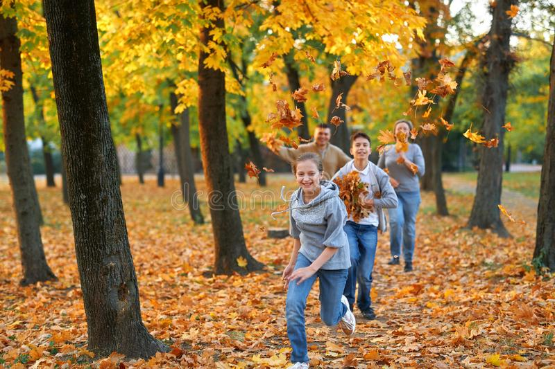 Happy family having holiday in autumn city park. Children and parents running, smiling, playing and having fun. Bright yellow stock photos