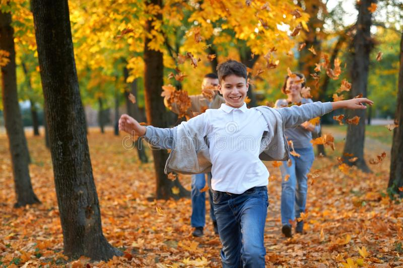 Happy family having holiday in autumn city park. Children and parents running, smiling, playing and having fun. Bright yellow royalty free stock image