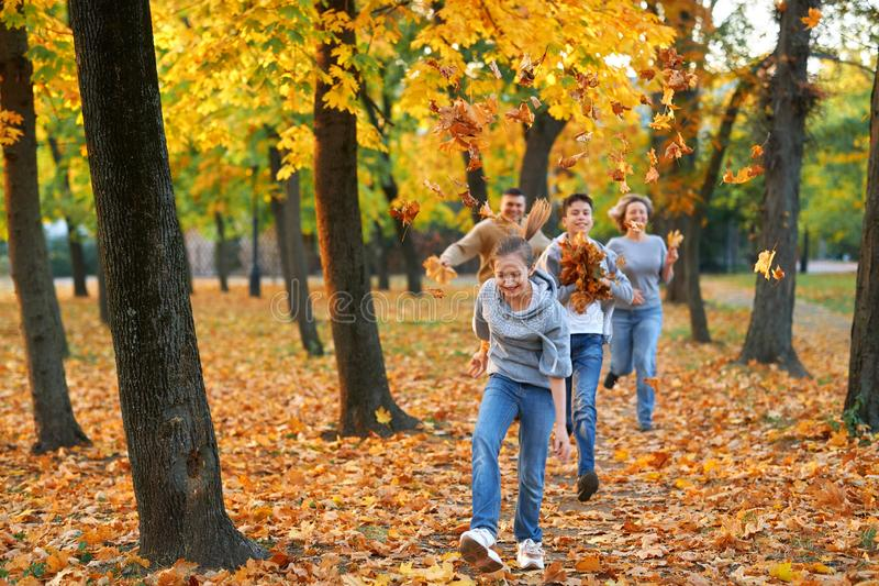 Happy family having holiday in autumn city park. Children and parents running, smiling, playing and having fun. Bright yellow stock photography