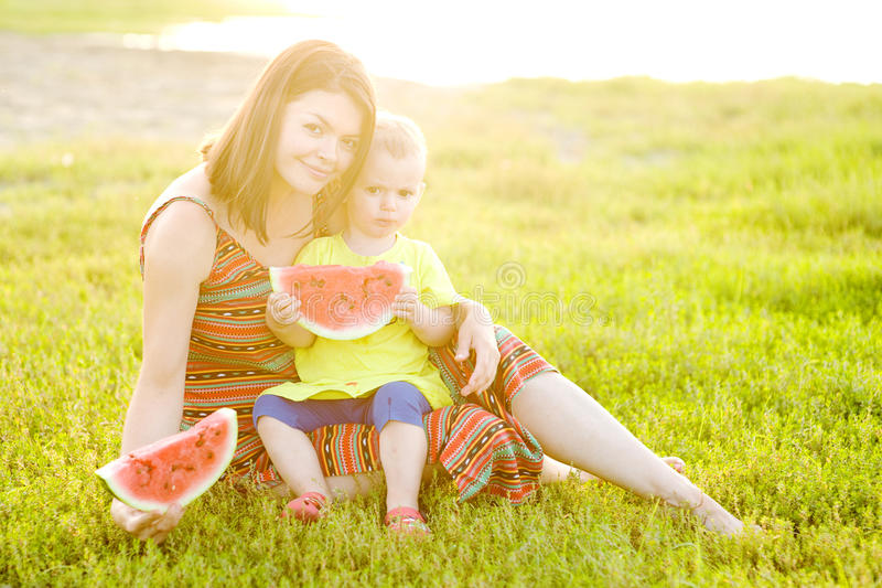 Happy family having picnic on green grass in park royalty free stock photography