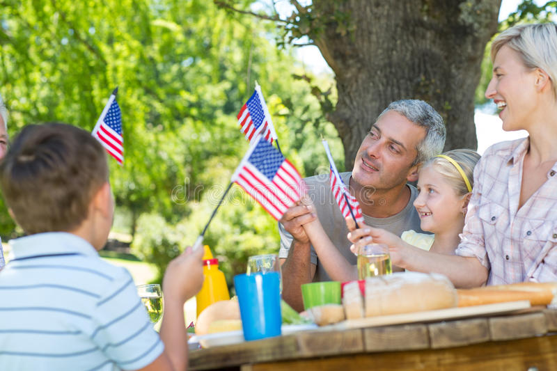 Happy family having picnic and holding american flag. On a sunny day royalty free stock photos