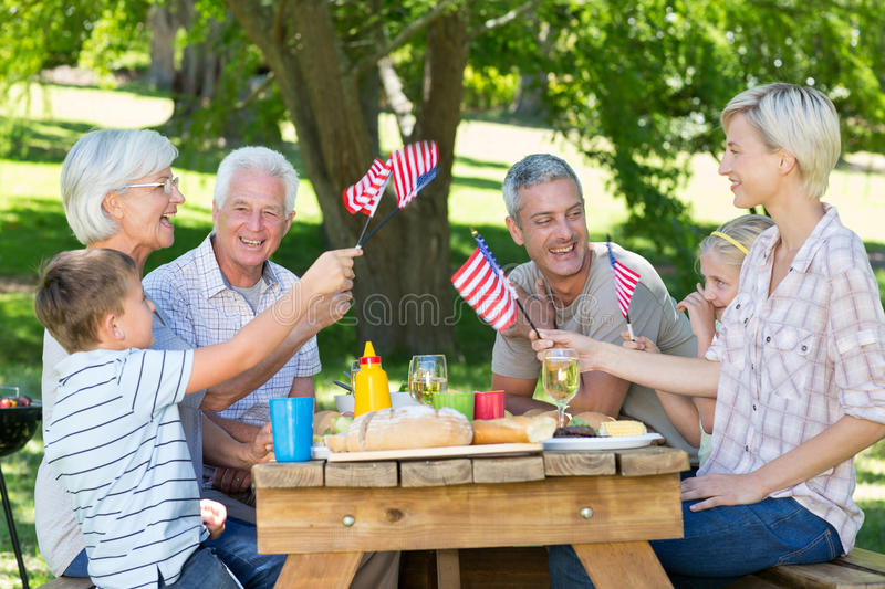 Happy family having picnic and holding american flag stock photos