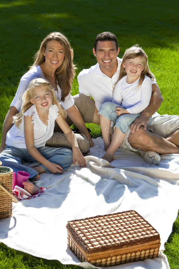 Happy Family Having Picnic In A Park. A young family with mother father and two blond daughters having a picnic in a sun bathed green park royalty free stock images