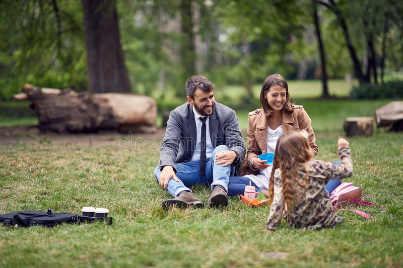 Happy family having a picnic in park after school royalty free stock images