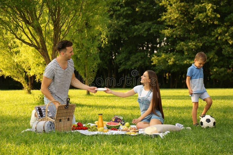 Happy family having picnic in park on sunny  day. Happy family having picnic in park on sunny summer day royalty free stock image