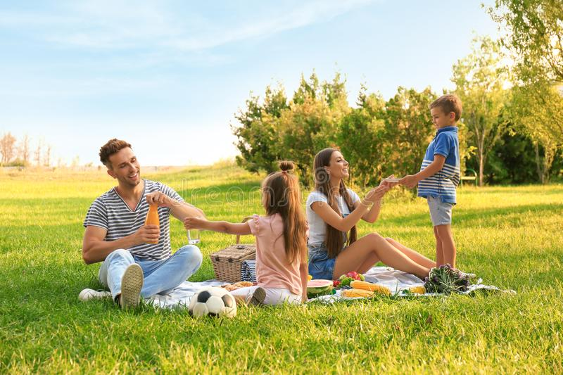 Happy family having picnic in park on summer day. Happy family having picnic in park on sunny summer day royalty free stock images