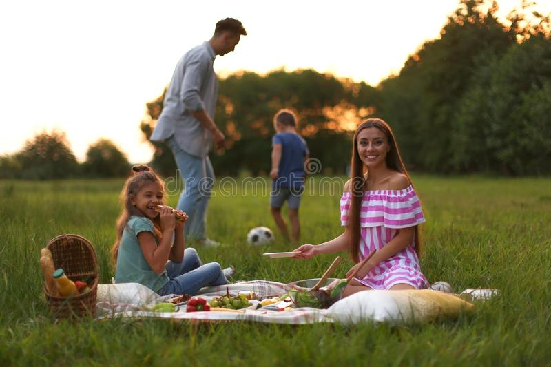 Happy family having picnic in park. At sunset stock images