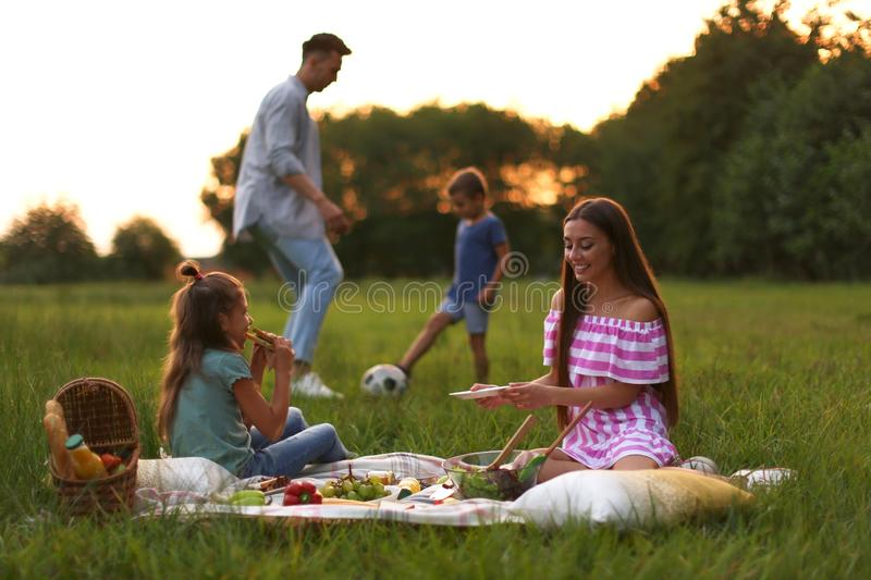 Happy family having picnic in park stock photo