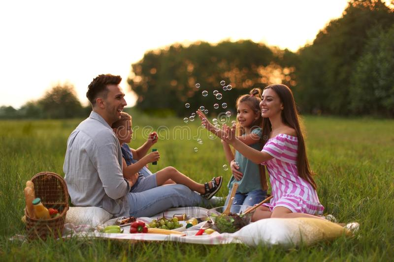 Happy family  picnic in park at sunset. Happy family having picnic in park at sunset stock image