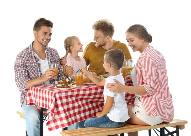 Happy family having picnic at table on white. Background stock photo