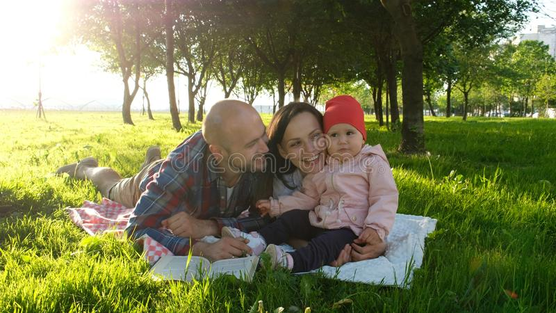 Happy family having a rest and kissing in the nature with the child at sunset in the park. Father kisses mother stock photos
