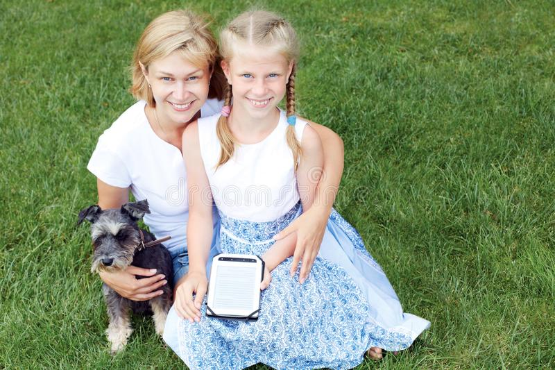 Happy family with his dog sitting on green grass and read e-book. Horizontal photo stock photography