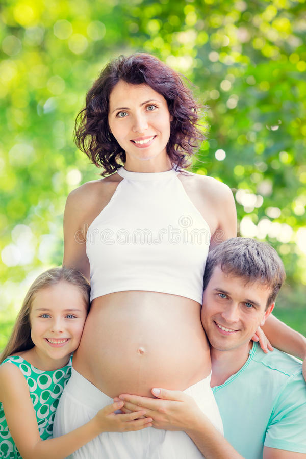Happy family holding belly of pregnant woman stock photography