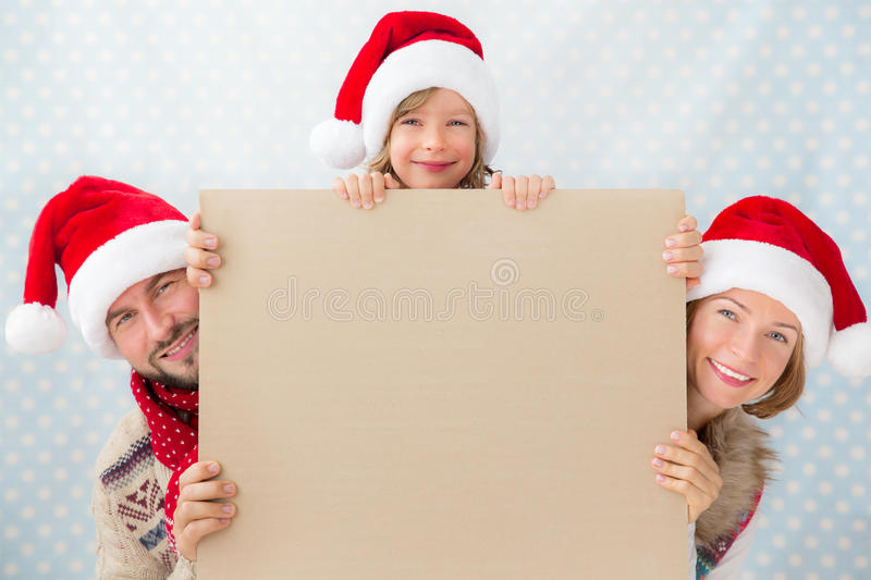 Happy family holding Christmas card stock image