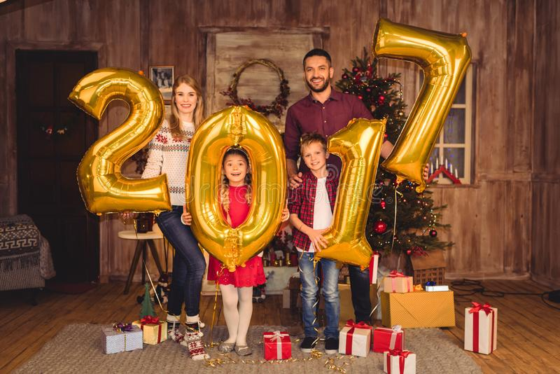 Happy family holding golden 2017 sign balloons and looking royalty free stock image