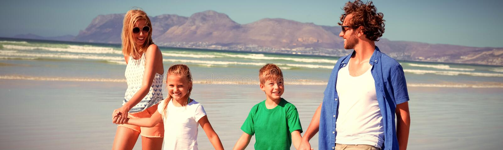 Happy family holding hands while walking at beach stock photography