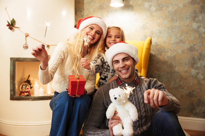 Happy family holding sparklers, looking at camera while celebrating Christmas eve at home royalty free stock photo